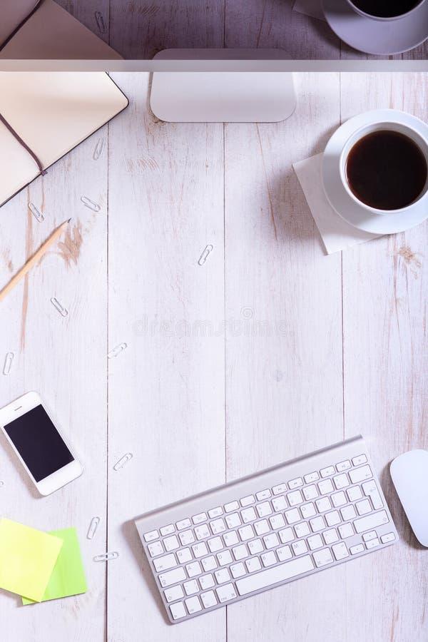 Arbetsskrivbord med telefonen för datorbildskärmtangentbord, modern skrivbords- smartphonePCutrustning och tillförsel på vitt trä arkivfoto