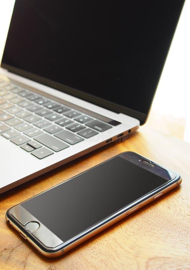 Arbetsställe med bärbara datorn och mobiltelefonen royaltyfria bilder