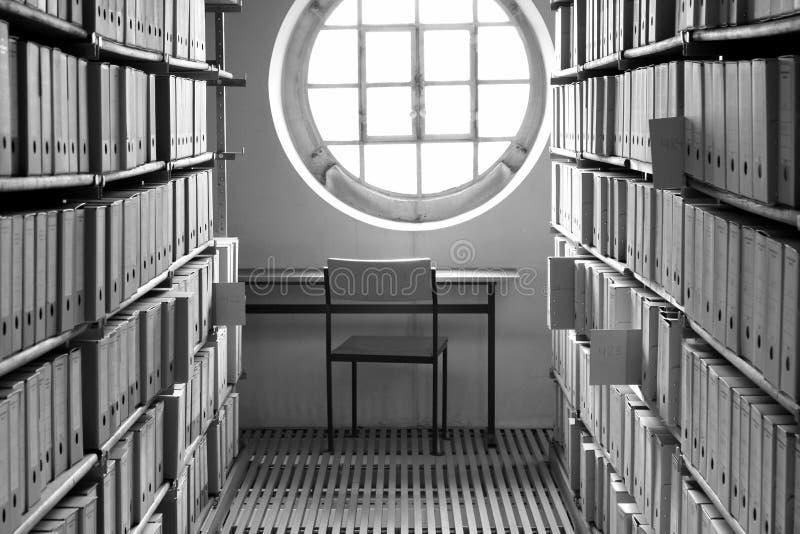 Arbetsställe med tabellen och stol under ett soligt fönster som omges av bokhyllor och kilometer av arkivaskar royaltyfria bilder