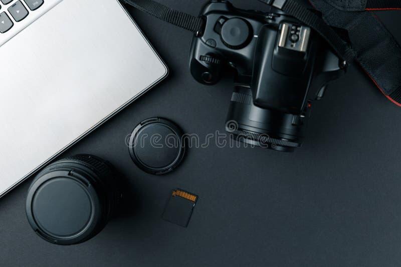 Arbetsutrymme p? den svarta tabellen av fotografen Minsta workspace med b?rbar dator-, kamera- och linskopieringsutrymme p? m?rk  royaltyfri bild