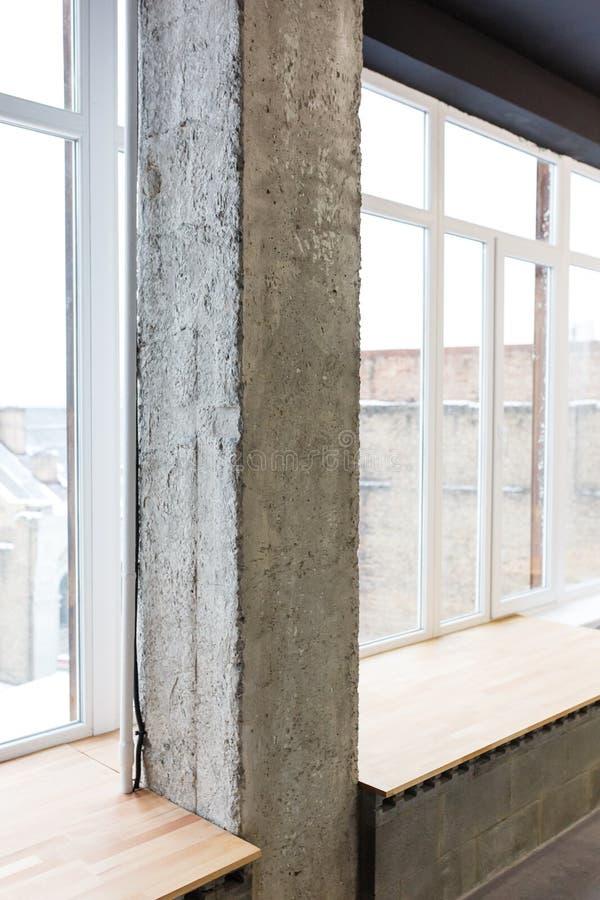 Arbetszon i kontoret i en vindstil med en konkret kolonn, ljusa väggar och en träbänk Stora ljusa fönster arkivbilder