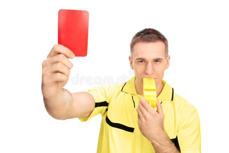 Arbiter pokazuje czerwoną kartkę i dmuchanie ogromny gwizd zdjęcia stock