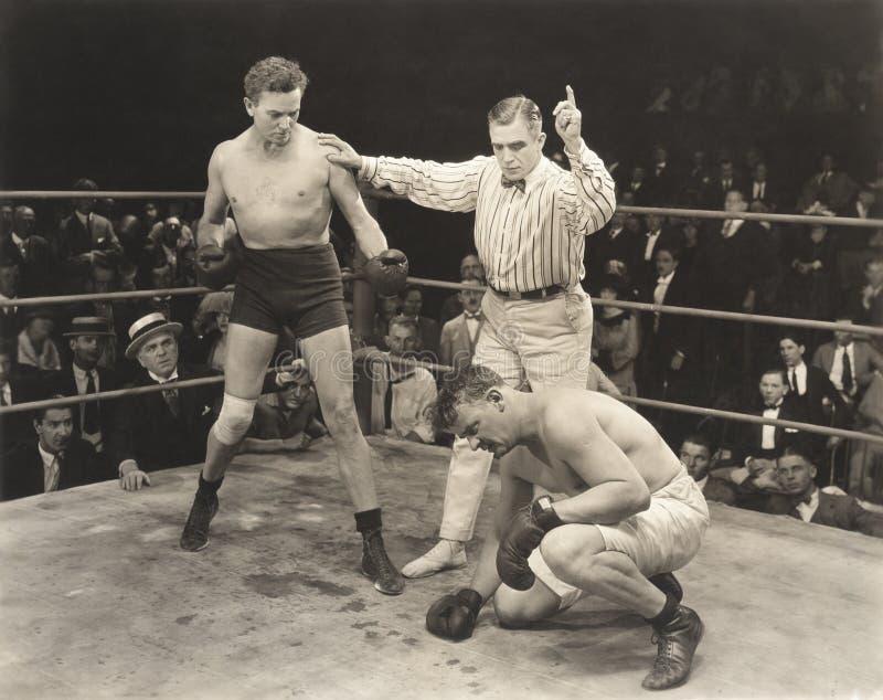 Arbitre comptant au-dessus du boxeur en anneau images libres de droits
