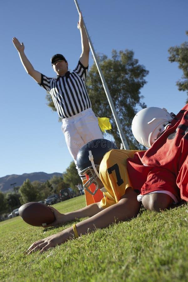 Arbitre signalant l'atterrissage au-dessus du joueur de football photographie stock