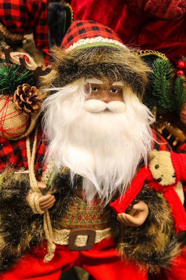 Arbolado santa con el sombrero de punto de la tela escocesa del chaleco y un oso de peluche con follaje imagen de archivo