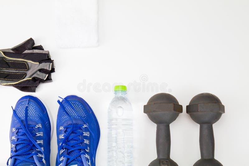 Arboleda de la aptitud y botella de agua del plástico, zapatos del deporte, pesa de gimnasia y toalla blanca en el fondo blanco fotografía de archivo libre de regalías