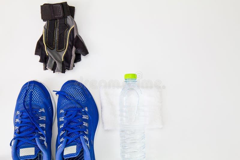 Arboleda de la aptitud y botella de agua del plástico, zapatos del deporte y blanco a imagen de archivo