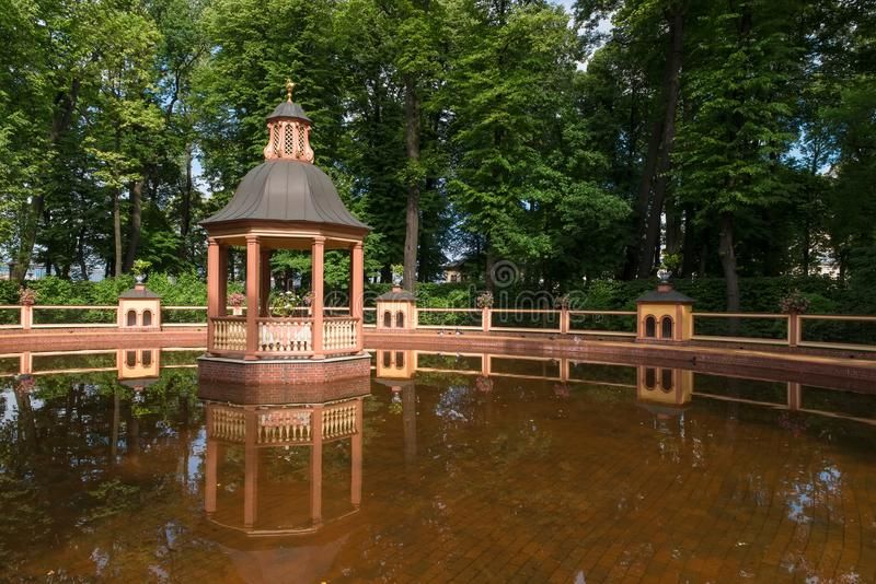 Arbor on the edge of the pond. SAINT PETERSBURG, RUSSIA - AUGUST 18, 2017: Bosket `Menagerie pond` 1720, according to the drawings of Jan Roosen; restored in stock photography