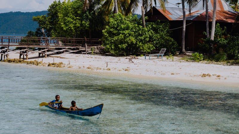 Arborek ö, Raja Ampat, Oktober 10, 2016: lokalungar i ett fartyg på den Arborek ön i Raja Ampat, västra Papua royaltyfri fotografi