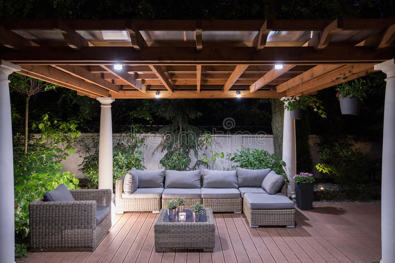 Arbour with comfortable garden furniture stock images