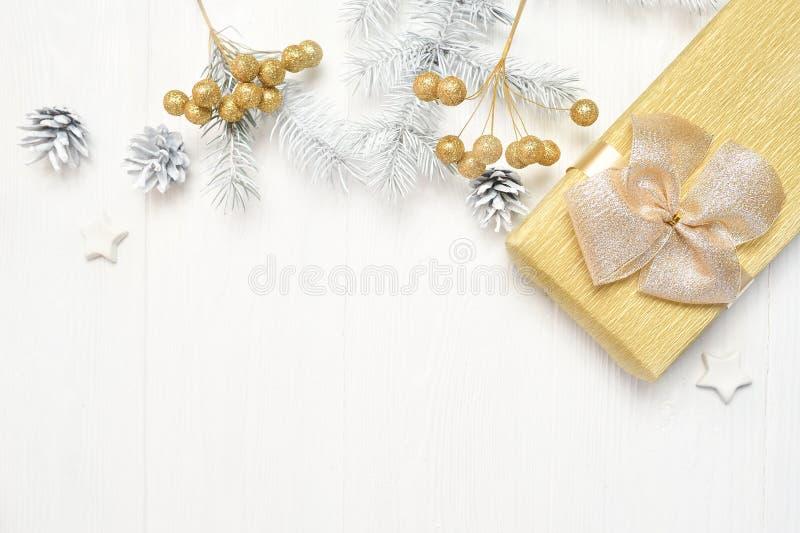 Arbre blanc de Noël de maquette, arc beige, boîte-cadeau et cône Configuration plate sur un fond en bois blanc, avec l'endroit po photographie stock libre de droits