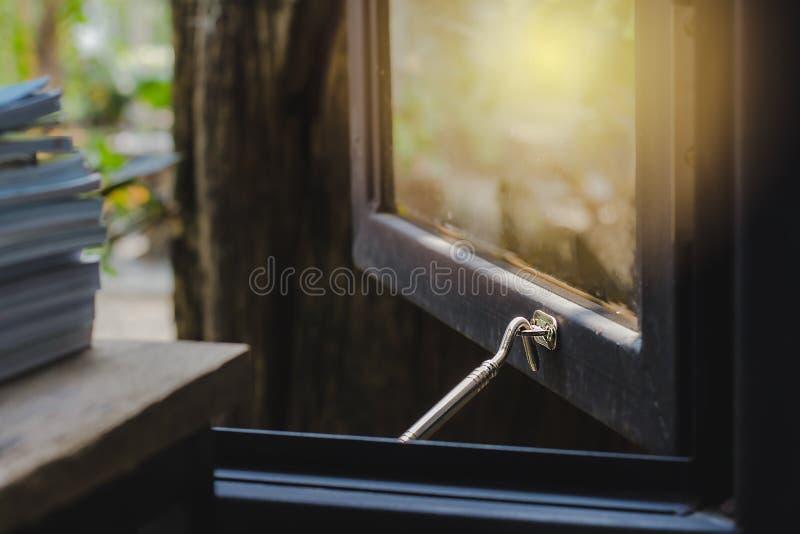 Arbre brouillé de fond d'image en dehors de la fenêtre La fenêtre est ouverte Il y a un livre sur le premier plan de table images libres de droits