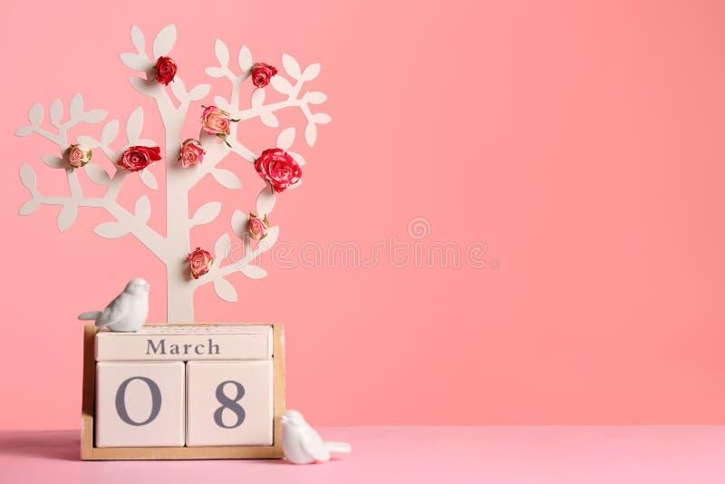 Arbre décoratif avec des fleurs et calendrier de bloc en bois sur la table sur le fond de couleur Jour heureux du ` s de femmes photos libres de droits
