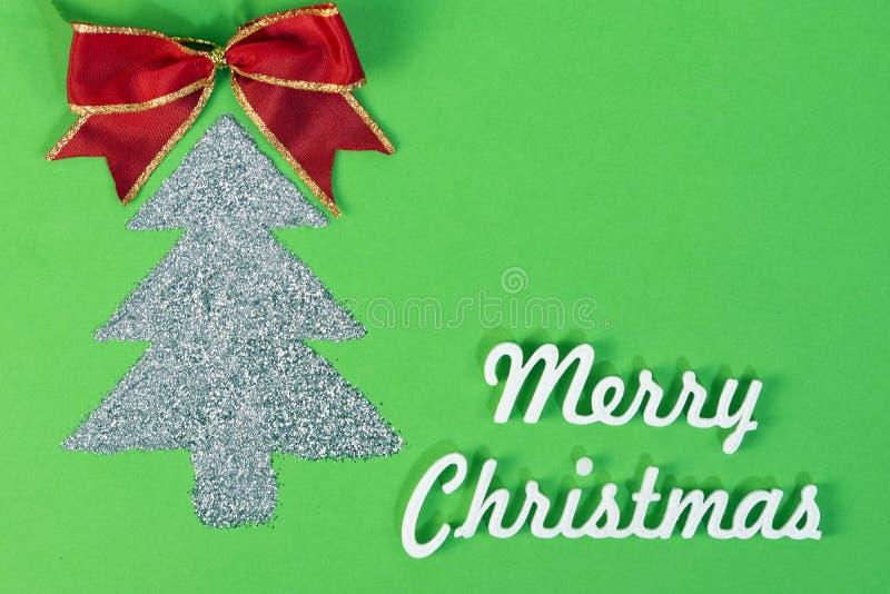Arbre de Noël éclatant avec de joyeux mots de noël sur fond vert, carte de noël avec espace de copie photo libre de droits
