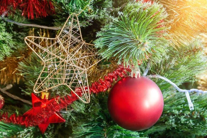 Arbre de Noël artificiel vert orné d'une étoile dans un cadre doré ; boule de matte rouge; et de guirlandes jaunes et rouges images libres de droits
