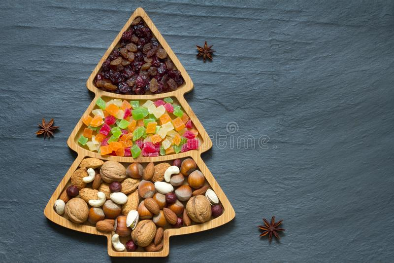 Arbre de Noël aux noix et fruits séchés sur fond noir images stock