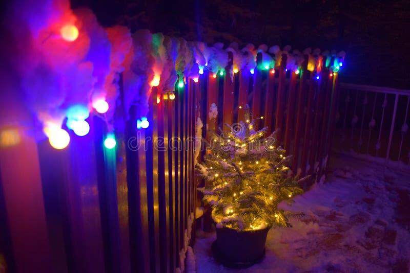 Arbre de Noël avec des lumières de Noël et neige sur un balcon photo stock