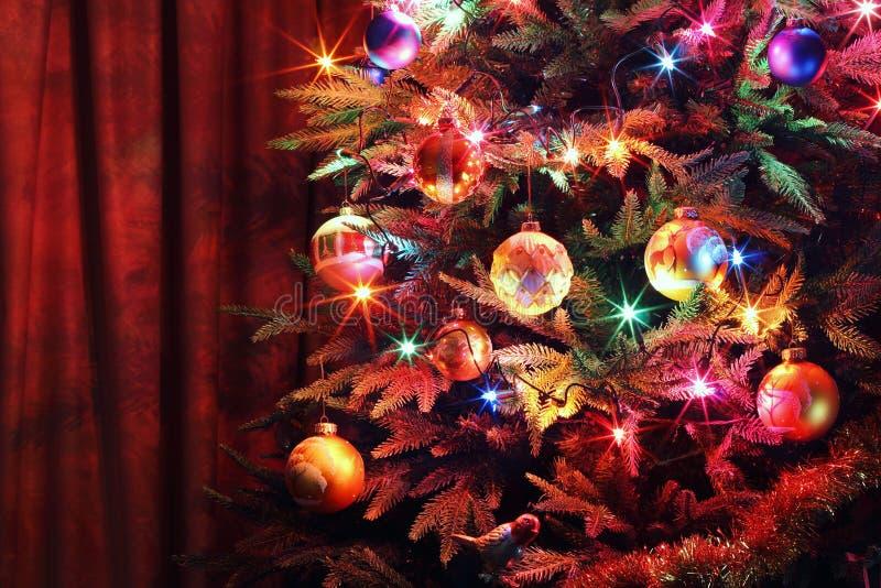 Arbre de Noël avec les boules, la guirlande rougeoyante et la tresse photographie stock