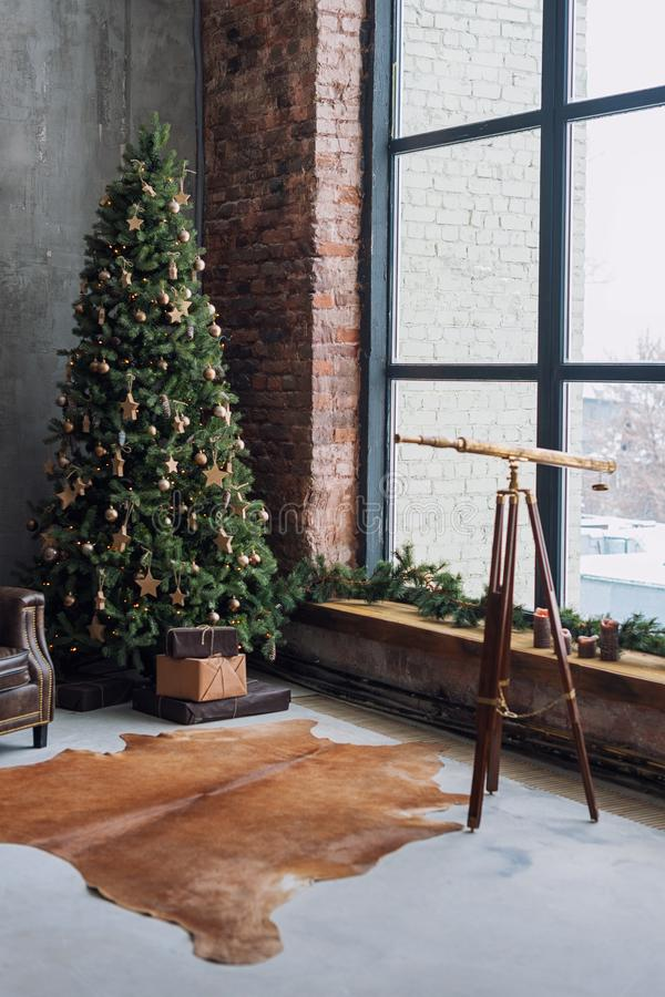 Arbre de Noël avec les décorations et les présents rustiques en bois sous lui dans l'intérieur de grenier image libre de droits