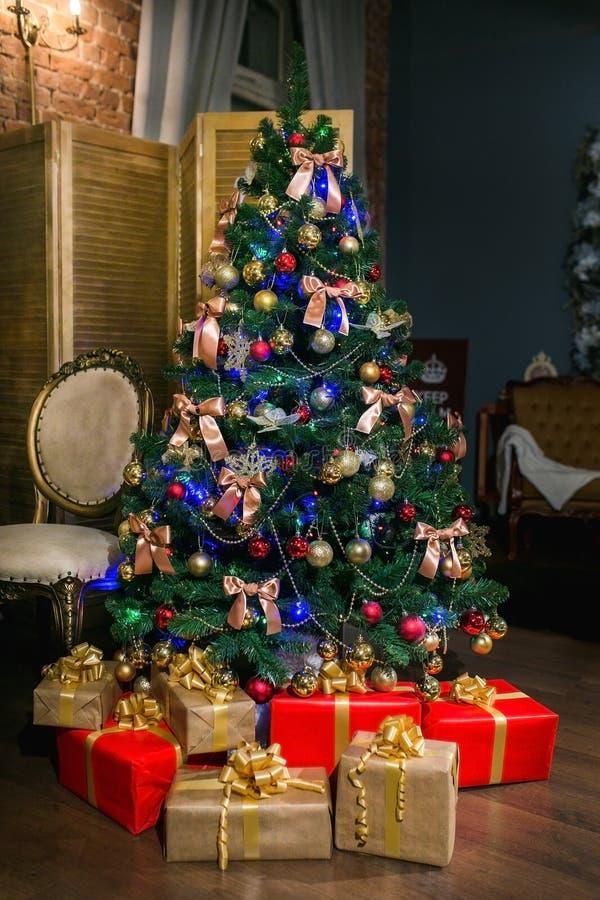 Arbre de Noël brillant décoré des boules et des arcs, avec des cadeaux sous lui dans le salon de style du grenier Soirée de Noël  image stock