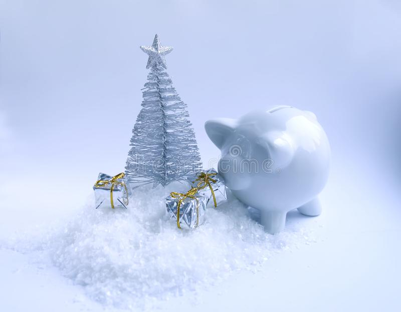 Arbre de Noël décoratif, tirelire en céramique de porc et boîte-cadeau sur le fond pelucheux de neige photographie stock libre de droits