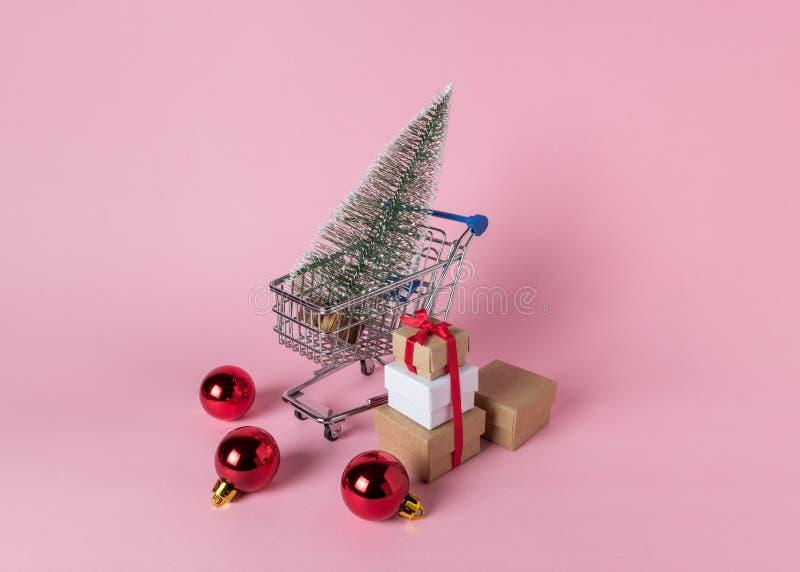 Arbre de Noël dans le caddie avec des boîte-cadeau sur le fond rose images stock