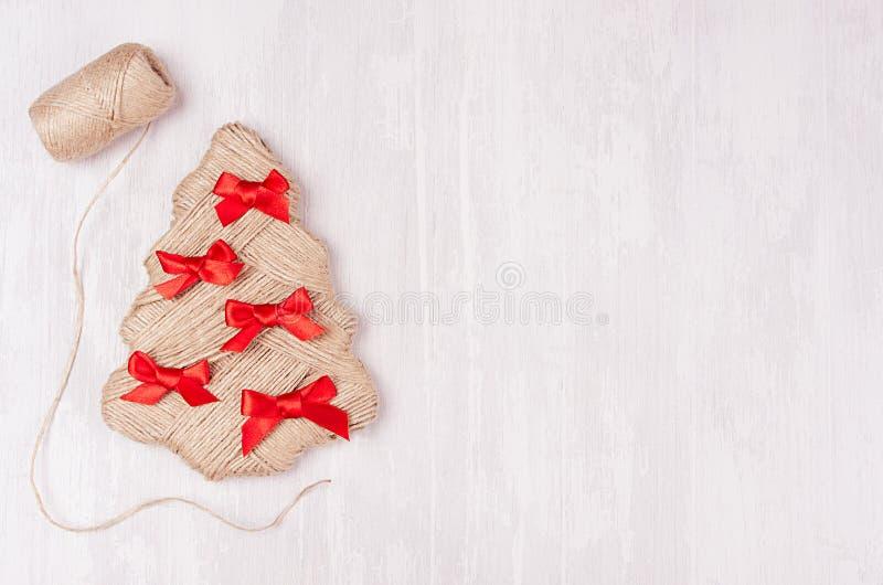 Arbre de Noël drôle avec les arcs rouges et ficelle en tant que frontière decoretive sur le fond en bois blanc mou images stock