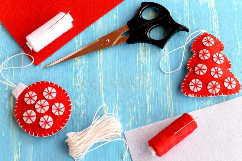 Arbre de Noël et boule, ciseaux, fil, aiguille, morceaux plats de feutre sur un fond en bois bleu avec l'endroit vide pour le tex photos stock