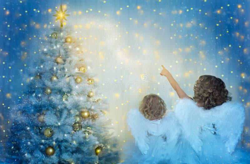 Arbre de Noël et enfants à la recherche de l'étoile, enfants avec des ailes comme anges de Noël dans la nuit photos stock