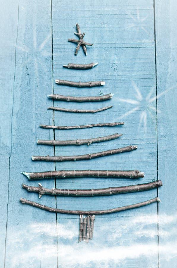 Arbre de Noël fait à partir des bâtons secs sur le fond en bois et bleu Image de neige et de flaks de neige Ornement d'arbre de N photographie stock