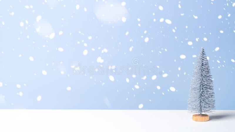 Arbre de Noël miniature dans la neige sur fond bleu Bannière de Noël avec espace de copie, carte de voeux du Nouvel An Style mini photo libre de droits