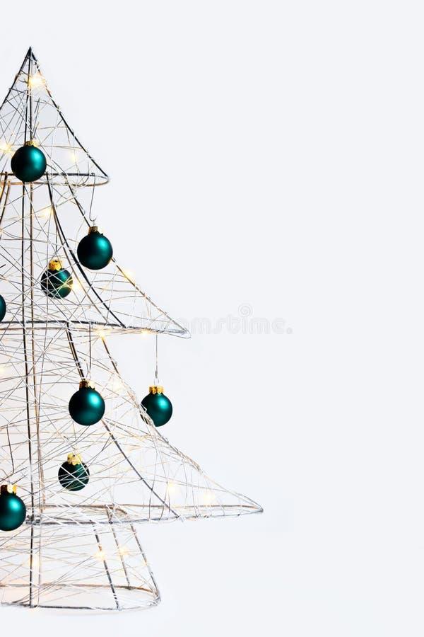 Arbre de Noël moderne fait de fil argenté en métal, enveloppé dans une guirlande rougeoyante et décoré des boules vertes photo stock