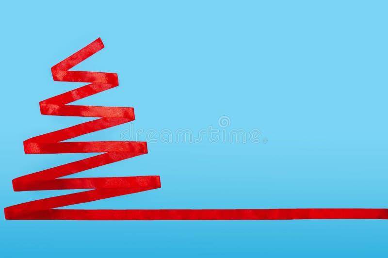 Arbre de Noël de ruban rouge sur le fond bleu Concept minimal de composition en nouvelle année Configuration plate Copiez l'espac images libres de droits