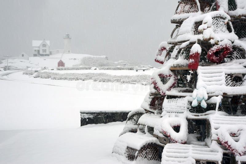Arbre de piège de homard de vacances couvert par neige par le phare photos libres de droits
