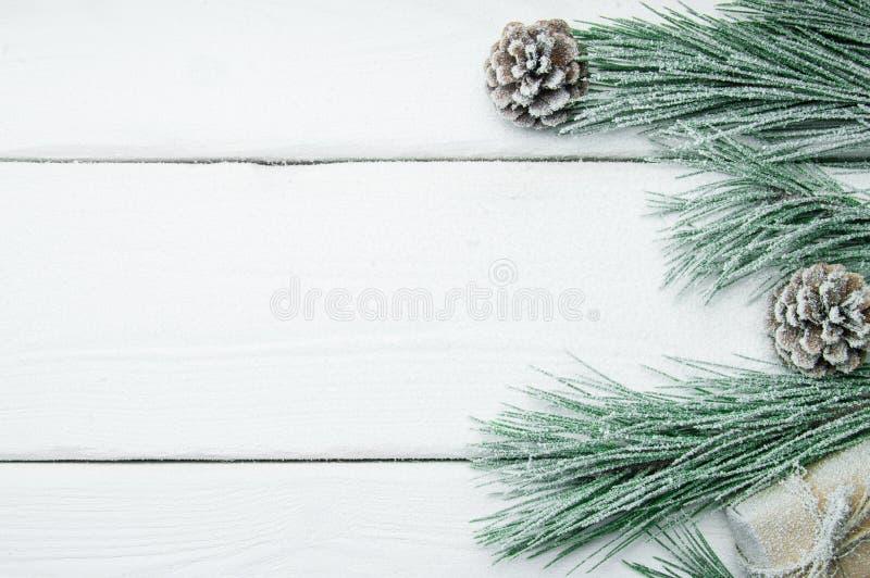 Arbre et cône de Noël de branche avec la neige sur la vue supérieure de fond en bois blanc de vintage images stock