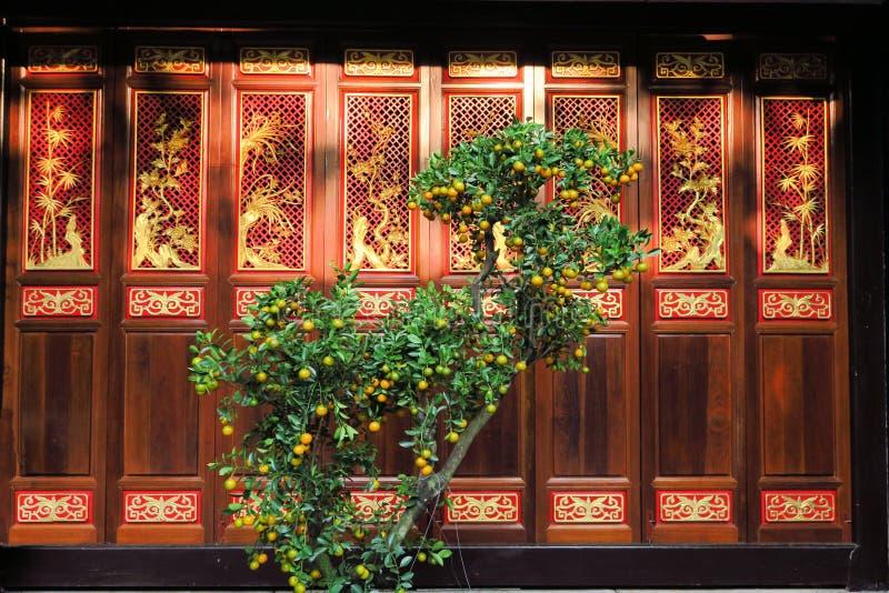 Arbre orange devant la porte en bois, bouddhiste image stock