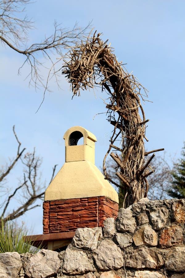 Arbre sec grand sans branches se penchant au-dessus du barbecue fait maison de brique devant le mur en pierre traditionnel avec l image libre de droits