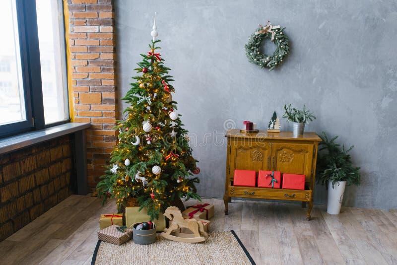 Arbre traditionnel de Noël avec des cadeaux en dessous et une commode classique en bois dans le salon de style loft, décoré photographie stock libre de droits