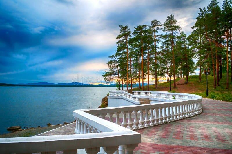 Arbres nuageux d'été de scène d'été au bord de la falaise et du lac sous le ciel orageux dramatique image stock