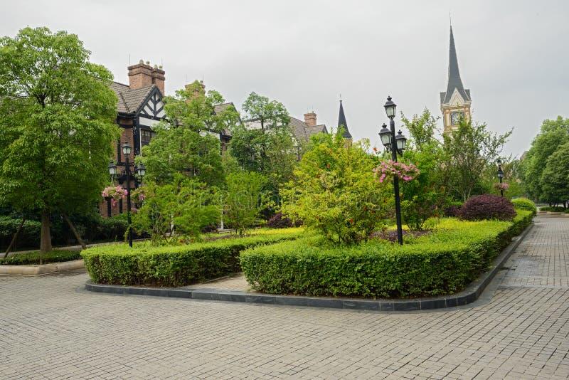 Arbustos antes de edificios del Europeo-estilo en primavera imagenes de archivo