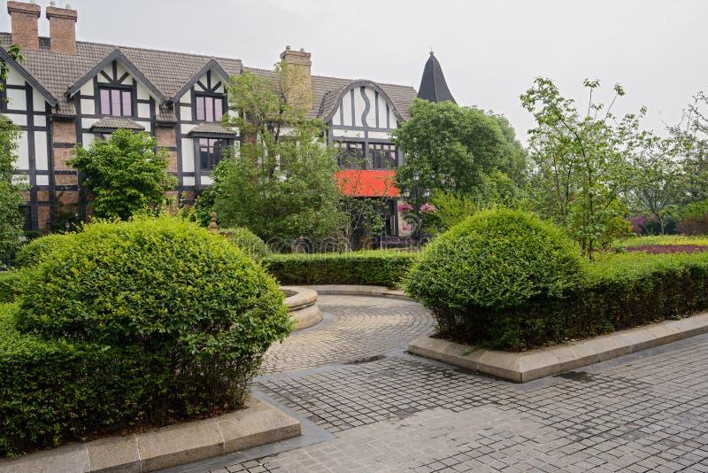 Arbustos y árboles antes del edificio europeo del estilo imágenes de archivo libres de regalías