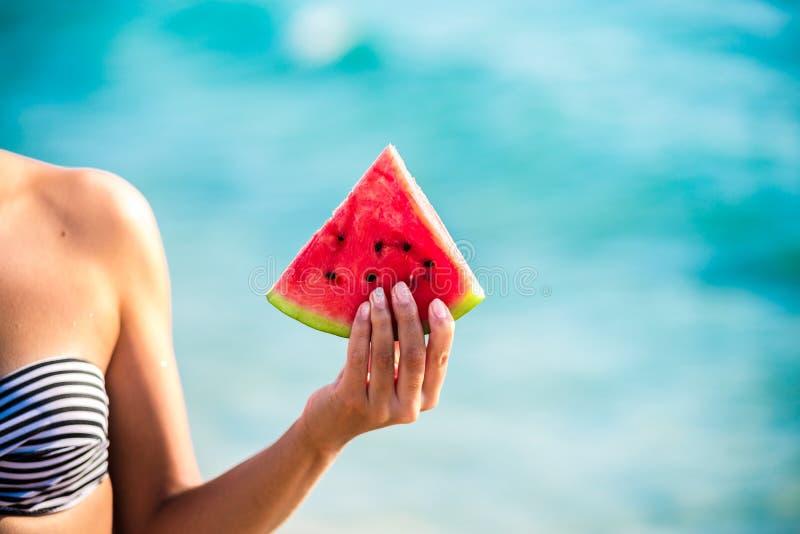 Arbuza plasterek w kobiecie oddawał morze - POV Lata plażowy pojęcie Tropikalnej owoc dieta obraz stock