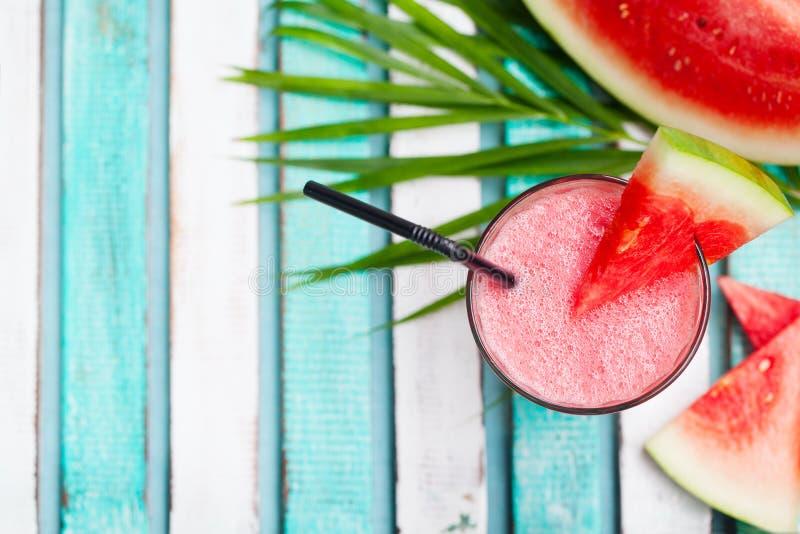 Arbuza smoothie, świeży sok na kolorowym drewnianym tle z palmowymi liśćmi Odgórny widok kosmos kopii obrazy royalty free