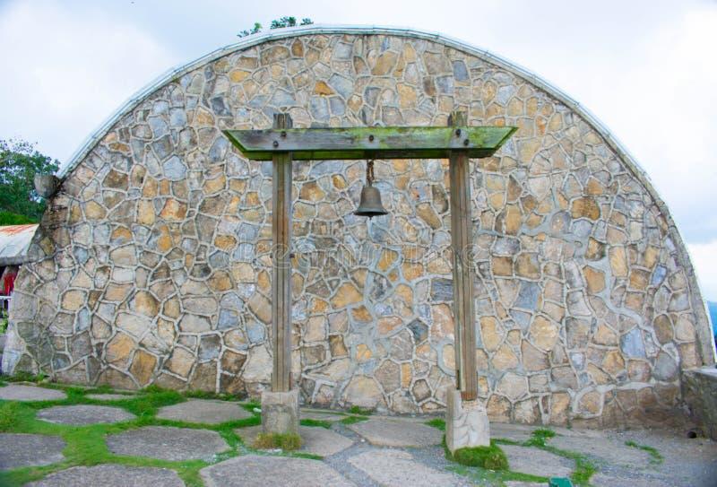 Arc avec un mur en pierre et une Bell accrochés dans deux Polonais en bois au centre image libre de droits