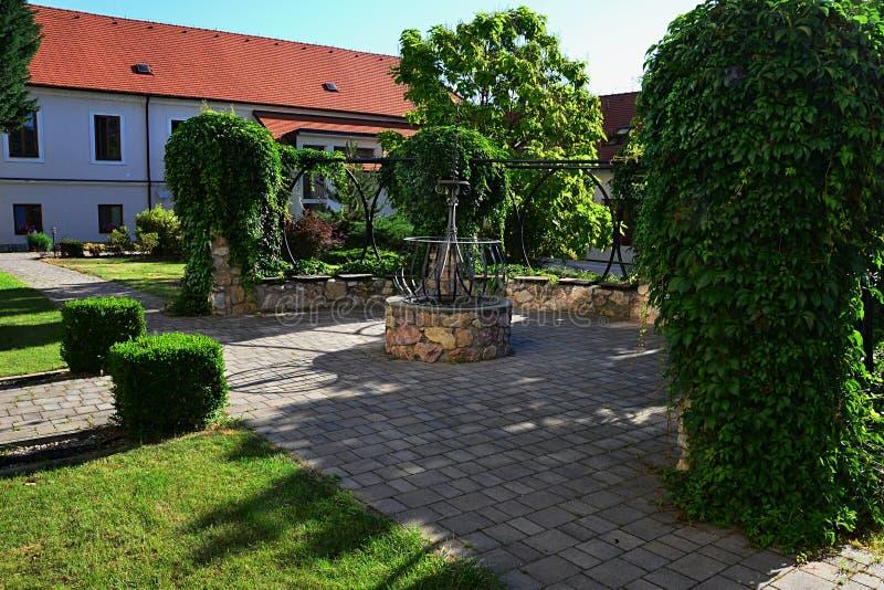 Arc décoratif de jardin avec la basse hélice de Hedera murral et grandissante en pierre en pierre de lierre sur la construction c photos libres de droits