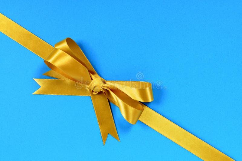 Arc d'or et ruban de cadeau sur le fond bleu, diagonal image stock