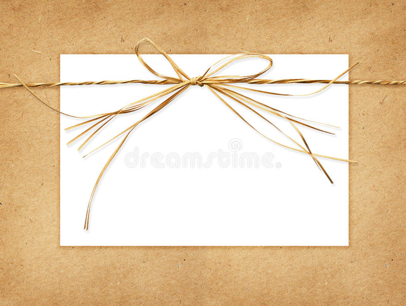 Arc de raphia et une carte attachée sur le papier de métier images libres de droits