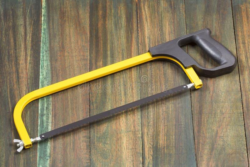 Arc de scie, outils de bricolage pour scier, jaune et noir sur la table en bois photos stock