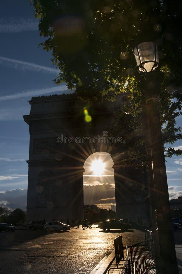 Arc de Triomphe avec le coucher du soleil au milieu images stock