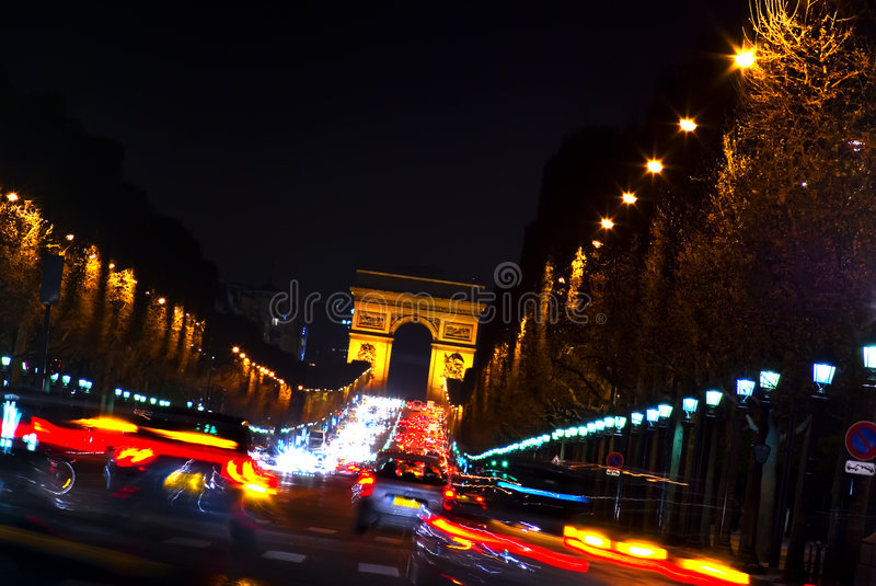 Arc de Triomphe and Champs Elysees, Paris, France. Creative night photograph looking from Place de la Concorde to the Arc de Triomphe with car headlight streaks stock image